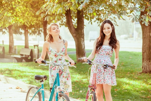 De twee jonge meisjes met fietsen in park