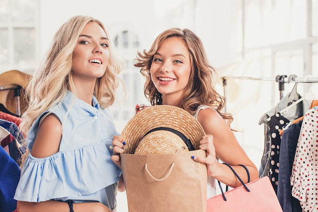 De twee jonge mooie meisjes kijken naar jurken en passen het terwijl ze in de winkel kiezen