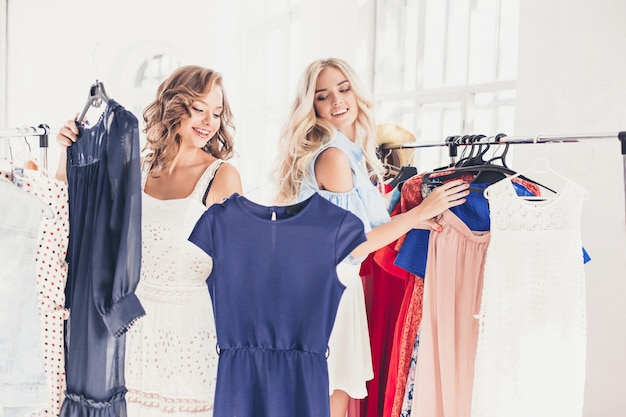 De twee jonge mooie meisjes kijken naar jurken en passen het terwijl ze kiezen in de winkel