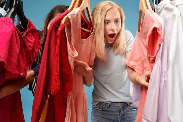 De twee jonge mooie vrouwen kijken naar jurken en passen het terwijl ze kiezen in de winkel