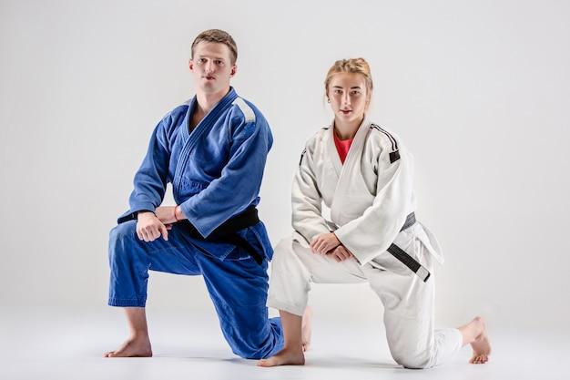 De twee judoka's strijders poseren op grijs