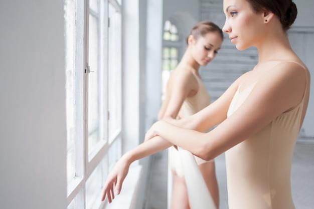 De twee klassieke balletdansers poseren in barre