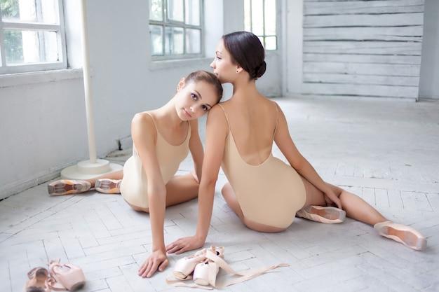 De twee klassieke balletdansers poseren op witte houten vloer