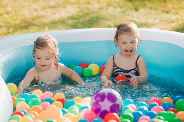De twee kleine baby meisjes spelen met speelgoed in opblaasbaar zwembad in de zonnige zomerdag