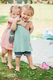 De twee kleine babymeisjes die tegen groen gras spelen