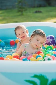 De twee kleine babymeisjes spelen met speelgoed in opblaasbaar zwembad in de zonnige zomerdag