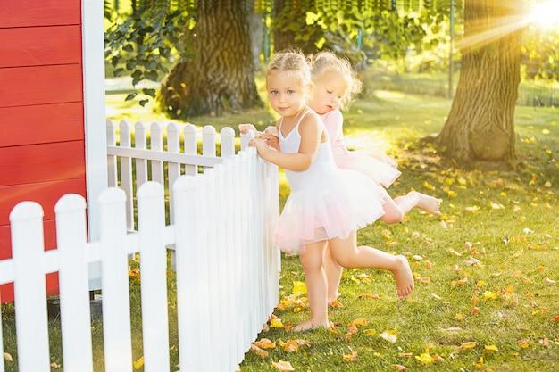 De twee kleine meisjes op speelplaats tegen park of groen bos