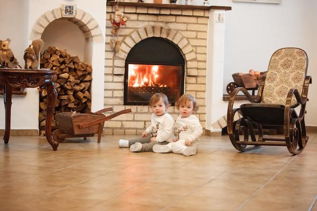 De twee kleine meisjes zitten thuis tegen de open haard
