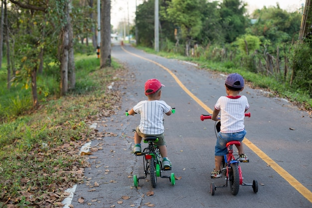 De twee lieve jongens rijden op de fiets laen.