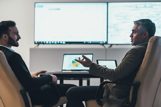 De twee mannen bespreken aan tafel in een modern kantoor