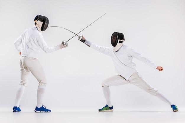 De twee mannen die een schermpak dragen oefenen met zwaard tegen grijs