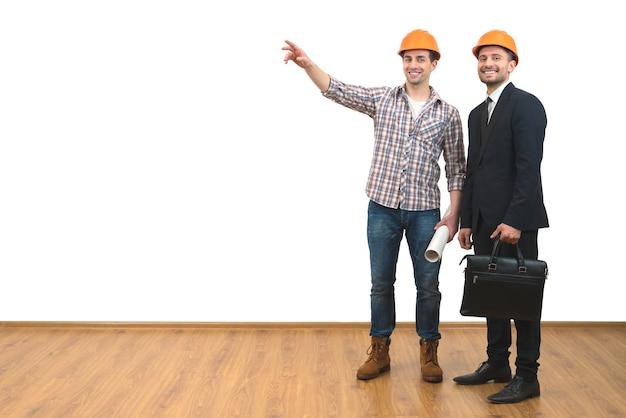 De twee mannen in helmen gebaar op de witte muur achtergrond