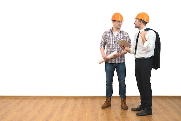 De twee mannen in helmen staan met een tablet op de witte muurachtergrond