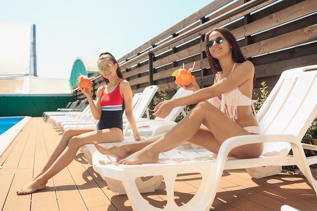 De twee meisjes spelen en ontspannen in een zwembad tijdens de zomervakantie
