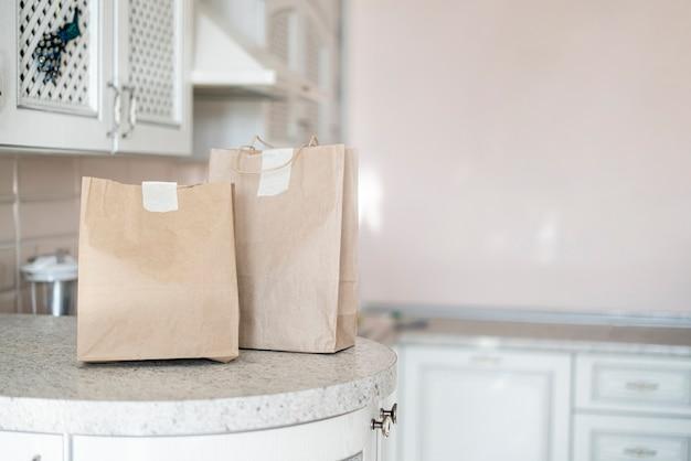 De twee papieren pakjes met eten aan huis geleverd