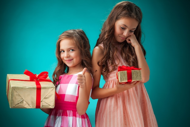 De twee schattige vrolijke kleine meisjes op blauwe achtergrond