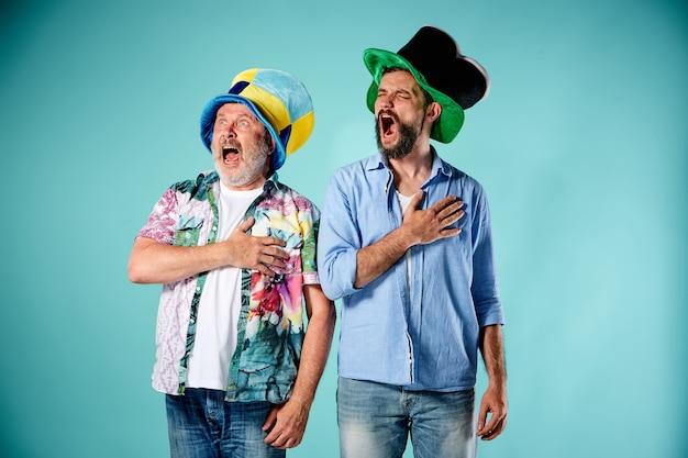 De twee voetbalfans zingen het volkslied over blauw
