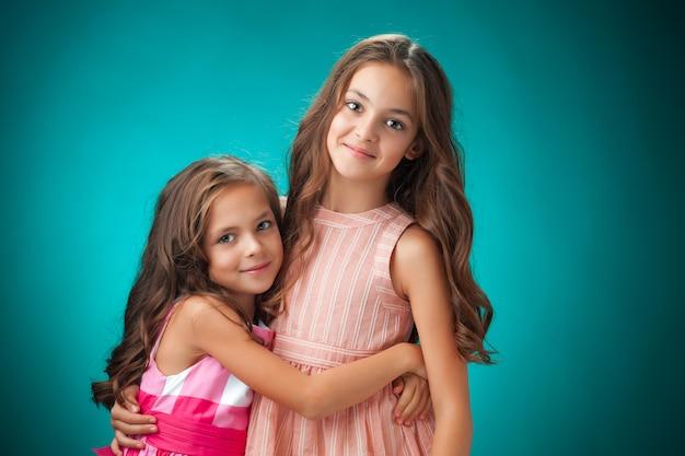 De twee vrolijke meisjes op oranje achtergrond