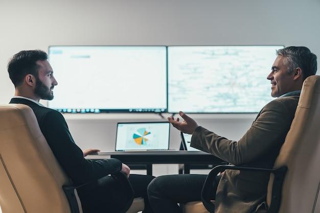 De twee zakenlieden bespreken aan de tafel bij een scherm