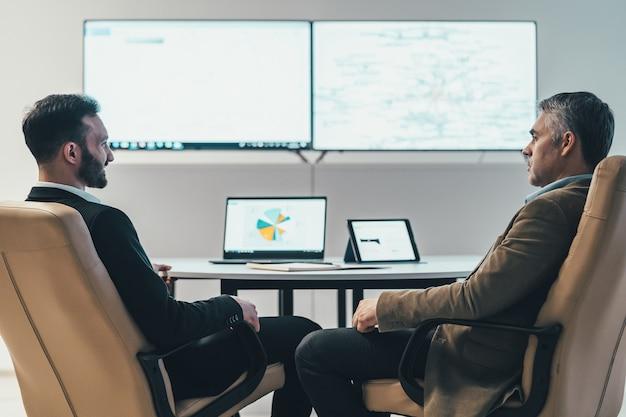 De twee zakenlieden die aan tafel bij een scherm zitten