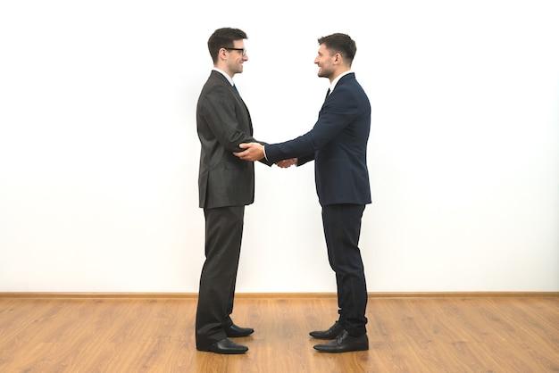 De twee zakenliedenhanddruk op de witte muurachtergrond