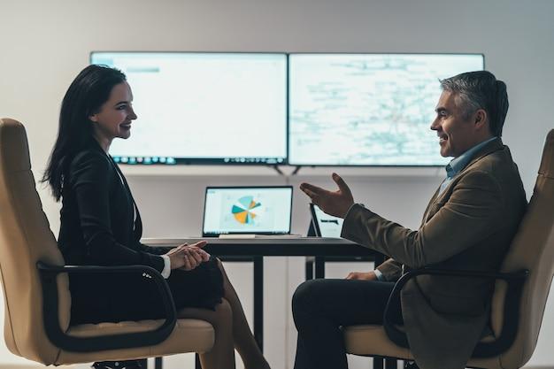 De twee zakenmensen bespreken aan de tafel bij een scherm