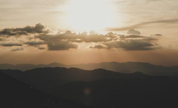 De tweede gouden zon schijnt 's avonds prachtig op de top van de berg.