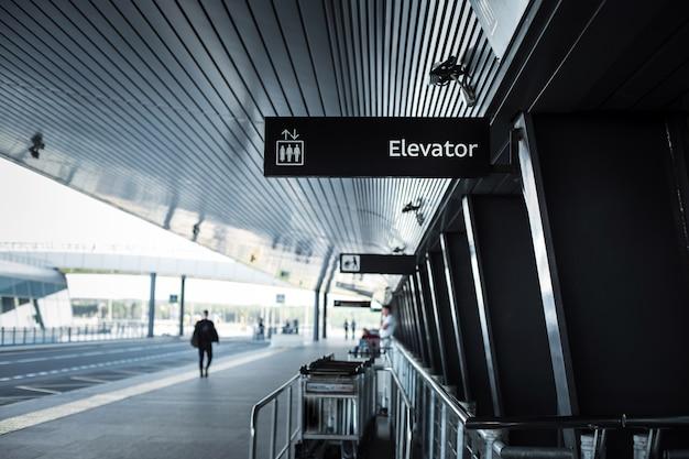 De uitgang van de luchthaven pulkovo in sint-petersburg - de bouw van de luchthaven met een bewegwijzering en bagagekarretjes en de weg erlangs.