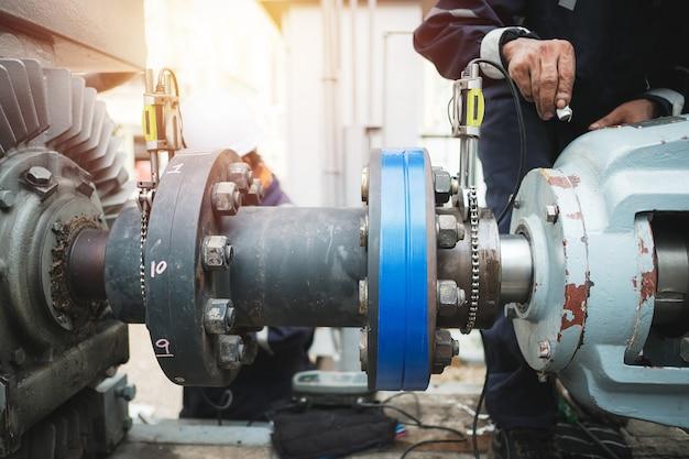 De uitlijningspomp van de technicusinspecteur en elektrische motor, die het werk in fabrieksconcept herstellen