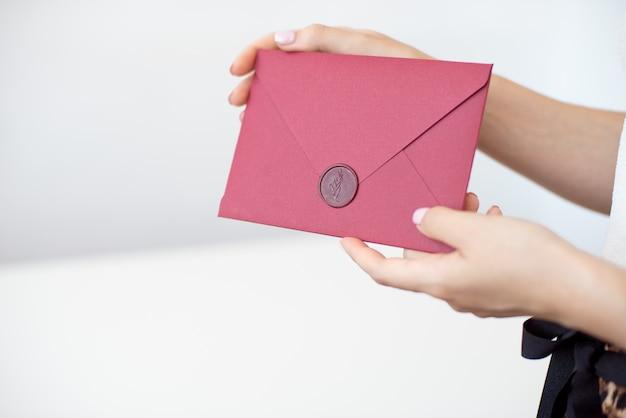 De uitnodigingskaarten van de vrouwengreep in hand. enveloppen in handenclose-up