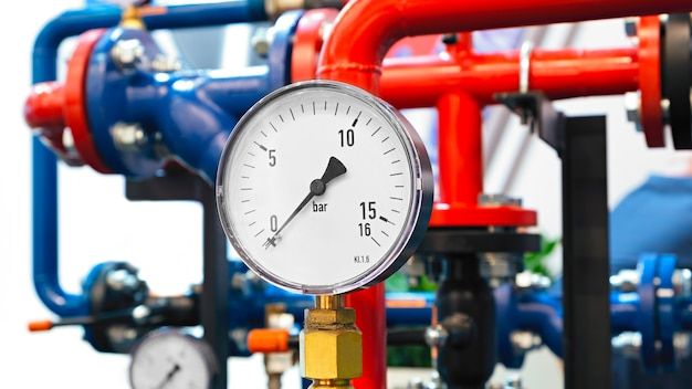 De uitrusting van het ketelhuis, - kleppen, buizen, manometers, thermometer. close-up van manometer, pijp, debietmeter, waterpompen en kleppen van verwarmingssysteem in een stookruimte.