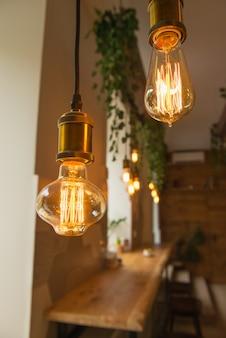 De uitstekende gloeilamp, sluit omhoog, koffieachtergrond, selectieve nadruk. interieur, details, decoratie, vintage thema