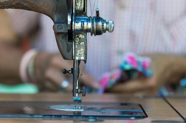 De uitstekende naaimachine op het onduidelijke beeldachtergrond van de manierontwerper