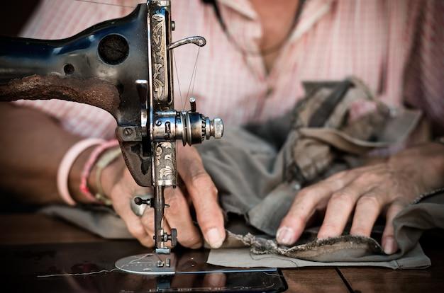 De uitstekende naaimachine op het onduidelijke beeldachtergrond van de oude mensenontwerper, uitstekende kleurentoon
