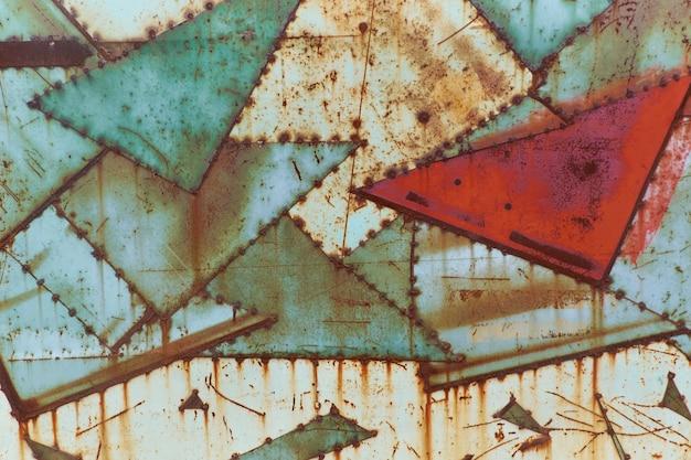 De uitstekende roestige muur van ijzerbladen textur geschilderd in groene en rode kleuren