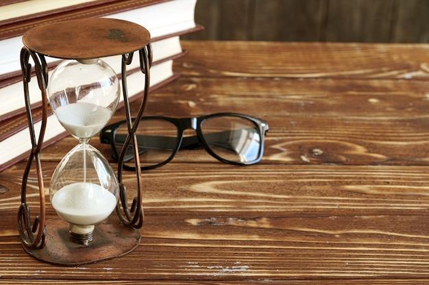 De uitstekende zandloper tegen een stapel oude boeken sluit omhoog