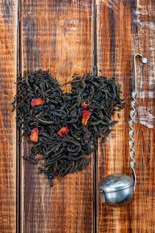 De uitstekende zeef dichtbij droge bladeren van zwarte thee maakt in hartclose-up. liefde