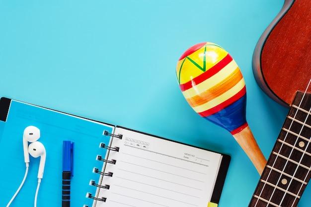 De ukelele met maracas, opende spiraalvormig notitieboekje, pen en oortelefoons op blauwe achtergrond