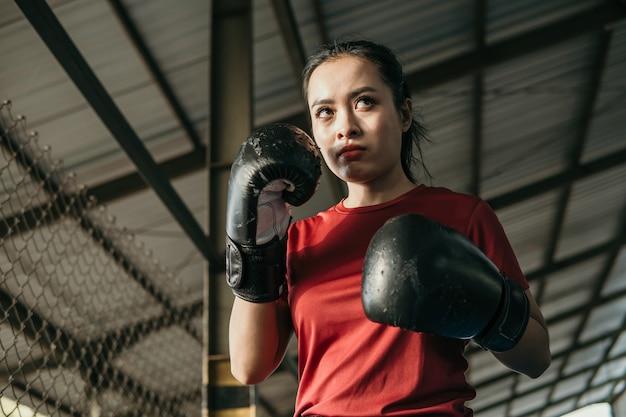 De ultieme vechter van de vrouw in bokshandschoenen met bewegingshanden verdedigen naast copyspace op de ringarena