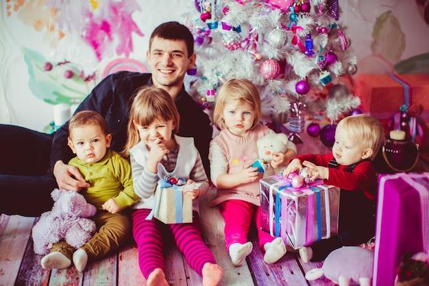 De vader die zijn kinderen omhelst dichtbij kerstboom