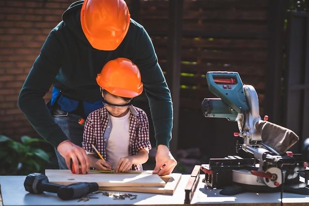 De vader die zijn zoontje leert gereedschap te gebruiken