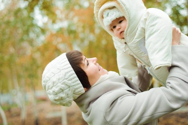 De vader en de moeder met baby kleedden zich in warme kleren in openlucht lopend op een zonnige dag. gelukkige familie tijd samen doorbrengen.