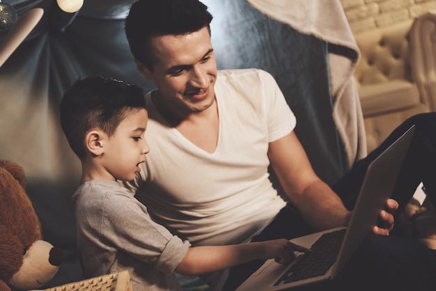 De vader en de zoon letten op video thuis op laptop bij nacht