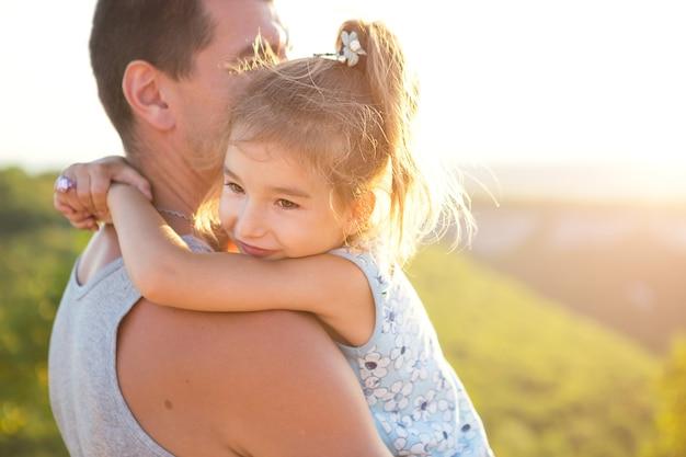 De vader en dochter omhelzen elkaar stevig, het meisje houdt de vader bij de nek vast
