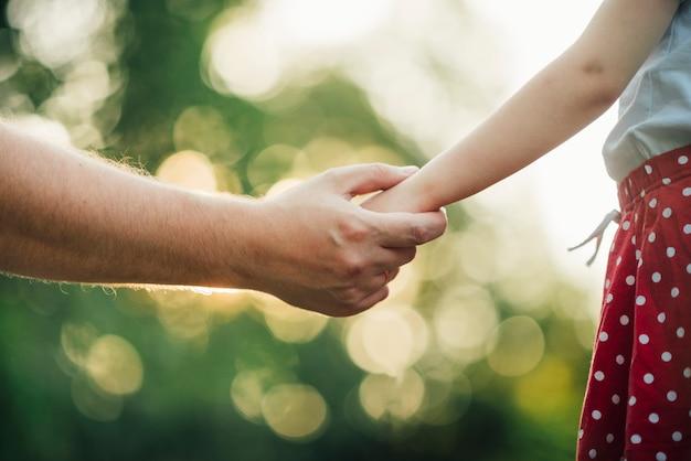 De vader en dochterholdingshanden sluiten omhoog