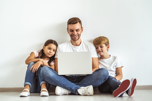 De vader en kinderen met een laptop op de grond