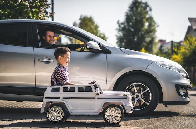 De vader en zoon rijden in hun auto