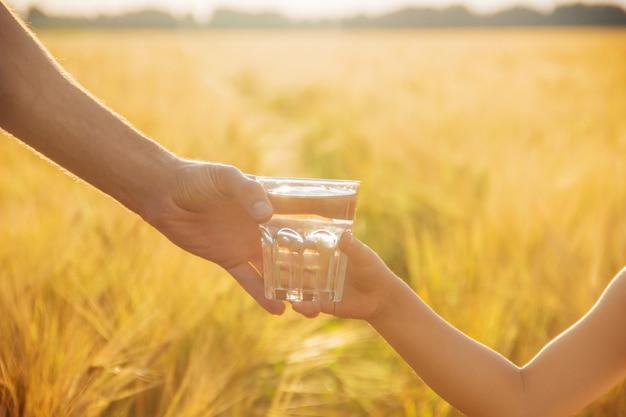 De vader geeft het kind een glas water. selectieve aandacht.