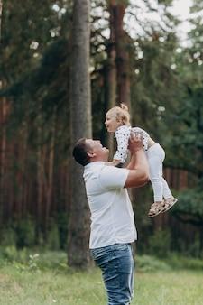 De vader geeft over en draait de dochter op de natuur op zomervakantie. vader en meisje spelen in het park op de zonsondergang tijd. meisje vliegt. concept van vriendelijke familie. detailopname. selectieve aandacht