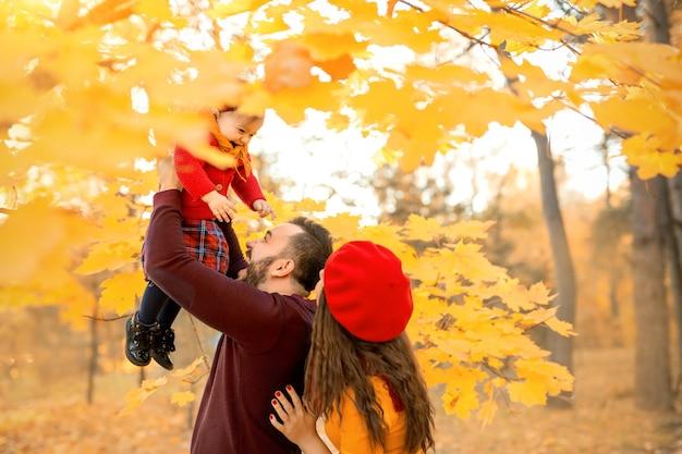 De vader gooit zijn lachende dochter omhoog in het oranje gebladerte van de esdoorntakken